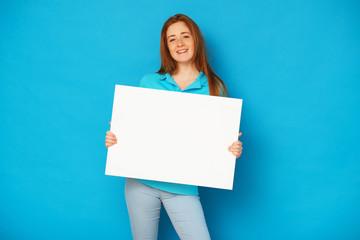 Fototapeta Ginger girl holding a whiteboard on blue background. obraz