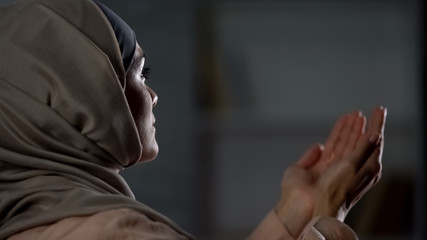 Attractive woman in hijab praying raising hands up, islamic culture thanksgiving