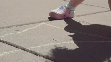 Wall Mural - Slow motion. Little girl is playing hopscotch on sunny Spring day suburbs.