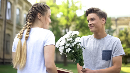 Teen boy presenting field flowers to teen girl, reading book in city garden