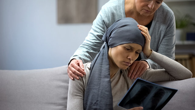 Woman with cancer looking at x-ray, mother supporting daughter, deterioration