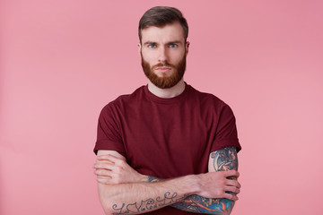 Close up of beautiful young man with ginger beard and tattooed hand, crossed arms and looking in camera without emotion isolated over pink background.