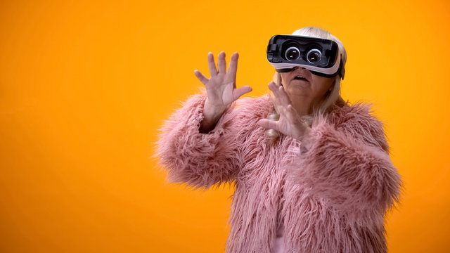 Senior woman in funny coat and VR headset playing video game, hi-end innovations