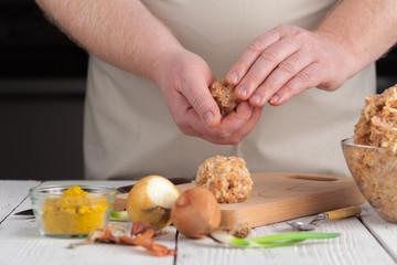 hands prepare meatballs from chicken meat