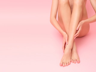 Picture of female, long legs isolated on pink background.