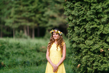 Portrait young girl in yellow dress with Flower wreath for head. Walking in park, Warm summer day.