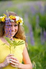 Young girl in yellow dress walking on meadow with lilac lupines. Warm summer day. Flower wreath for head