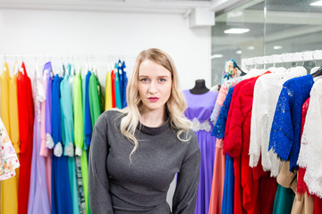 Portrait of a girl on the background of clothes on hangers in the clothing store. Happy young woman choosing clothes. Sale, fashion, consumerism concept