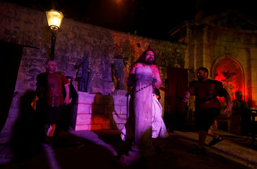 "Actors take part in the scene of the flogging of Jesus Christ during the interactive street theatre Passion play ""Il-Mixja"" (The Way), one of a series of Holy Week activities in the run-up to Easter, in Santa Venera"