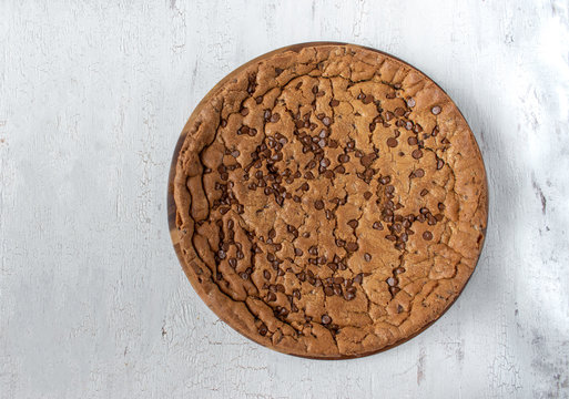 large chocolate chip cookie cake on rustic white background flat lay