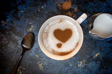 flat lay of coffee topped with cream and coffee art of heart in cinnamon
