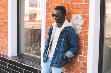 Wall Mural - Stylish african man wearing jeans jacket, backpack posing on city street, brick wall background