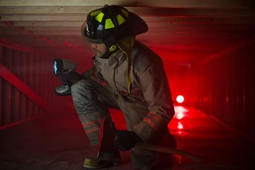 Firefighter in confined spaces looks around with large flashlight