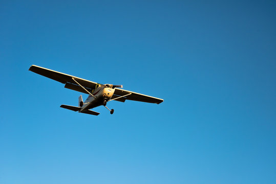 Small airplane approaching with blue sky
