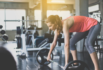 Sporty women exercise with barbell,Female does the exercising at gym