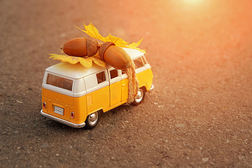 usual classic yellow bus on asphalt road. toy retro bus with maple leaf and acorns, autumn season. Soft focus.