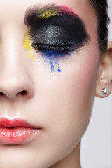 Female closed eye with unusual artistic painting makeup