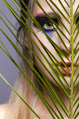 Female portrait with palm branch leaves on foreground and beauty face makeup.