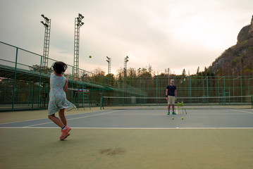Portrait Asian girl plays tennis with her father and coach at outdoor court with stone mountain and forest background