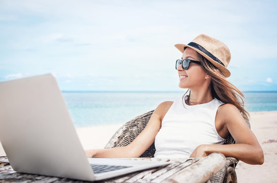 Young woman freelancer working on the beach