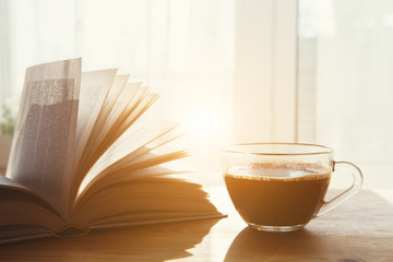 cup on morning coffee and open book on wooden table