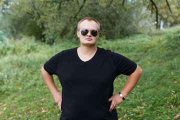 portrait of a fat guy in sunglasses on nature