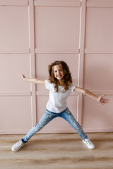 cute little girl posing on a pink background