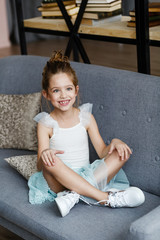 positive little girl sitting on the sofa at home