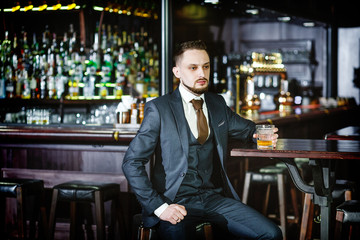serious man in a stylish suit drinking whiskey in a pub. Stylish handsome male in an elegant suit holds a glass of whiskey at bar counter background.