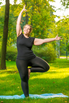 fat cheerful woman doing yoga in the park, plus size model