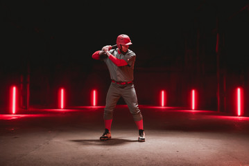 Caucasian professional baseball player batter posing against dark background in a large abandoned warehouse. 4K UHD 60 FPS SLOW MOTION