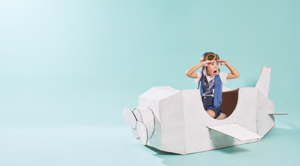 Little cute girl playing with a cardboard airplane. White retro style cardboard airplane on mint green background . Childhood dream imagination concept . Horizontal format .