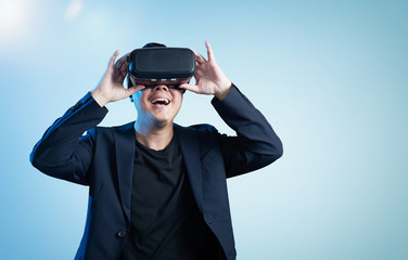 Asian businessman be excited during the view of VR experience with blue background