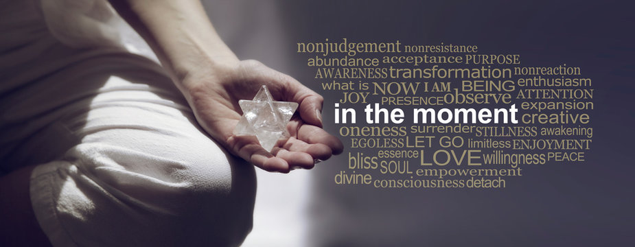 In the Moment Meditation Word Cloud Banner - Female sitting in Lotus Position on left side with sunlight streaming in holding a Merkabah crystal meditating and a relevant word cloud on right side