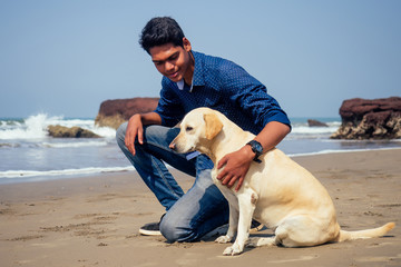 Young handsome indin man wearing black shirt and sunglasses, sitting on the beach with the white dog in Goa beach happy morning time.pet travel puppy training