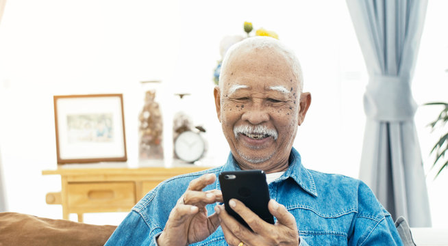 Asian Senior man with white mustache talking with smart phone.