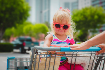 shopping with kids- cute little girl in shopping cart in the city