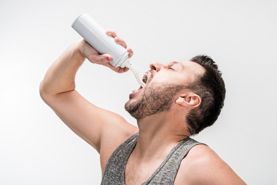 chubby man in grey tank top spraying whipped cream in mouth on white