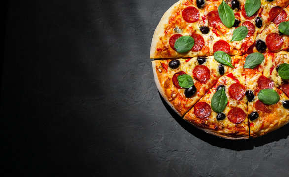 Pepperoni Pizza with Mozzarella cheese, salami, olive, pepper, Spices and Fresh spinach. Italian pizza on Dark grey black slate background