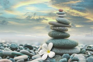 Photo sur Plexiglas Zen pierres a sable stone pyramid with a white magnolia flower on a pebble beach at sunset