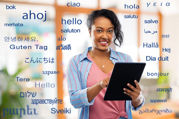 technology, translation and people concept - happy african american woman using tablet computer...