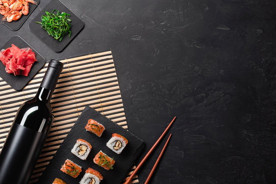 Set of sushi and maki with a bottle of wine on stone table. Top view