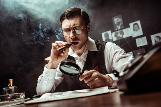 Detective in glasses smoking cigar and reading newspaper with magnifier in office