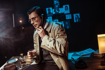 Detective in glasses talking on telephone and holding glass of cognac