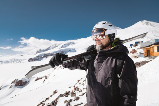 Portrait bearded male skier aged against background of snow-capped Caucasus mountains. An adult man wearing ski googles mask and helmet skis on his shoulder looks mountains. Ski resort concept