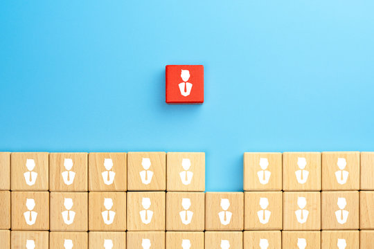 Leadership concept with businessman icon on red wood blocks standing out from the group on blue back ground
