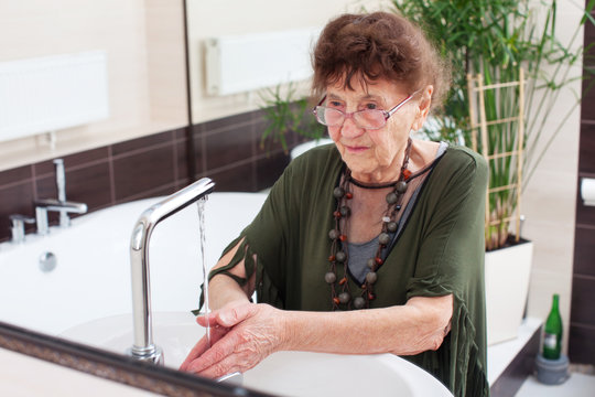 Elderly old woman washes her hands