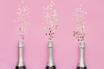Three Champagne bottles with confetti stars on pink background. Copy space, top view