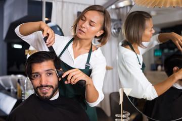 woman hairdresser shaving hair of smiling man
