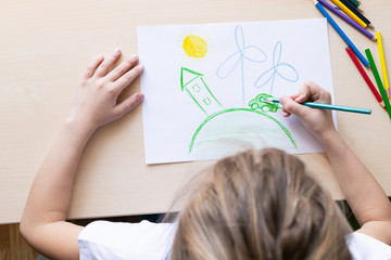 A girl draws with pencils a green house planet car wind power plants. Concept of ecology and environmental protection.